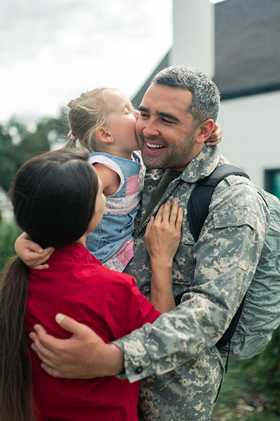 Military father receiving kiss from daughter held by mother
