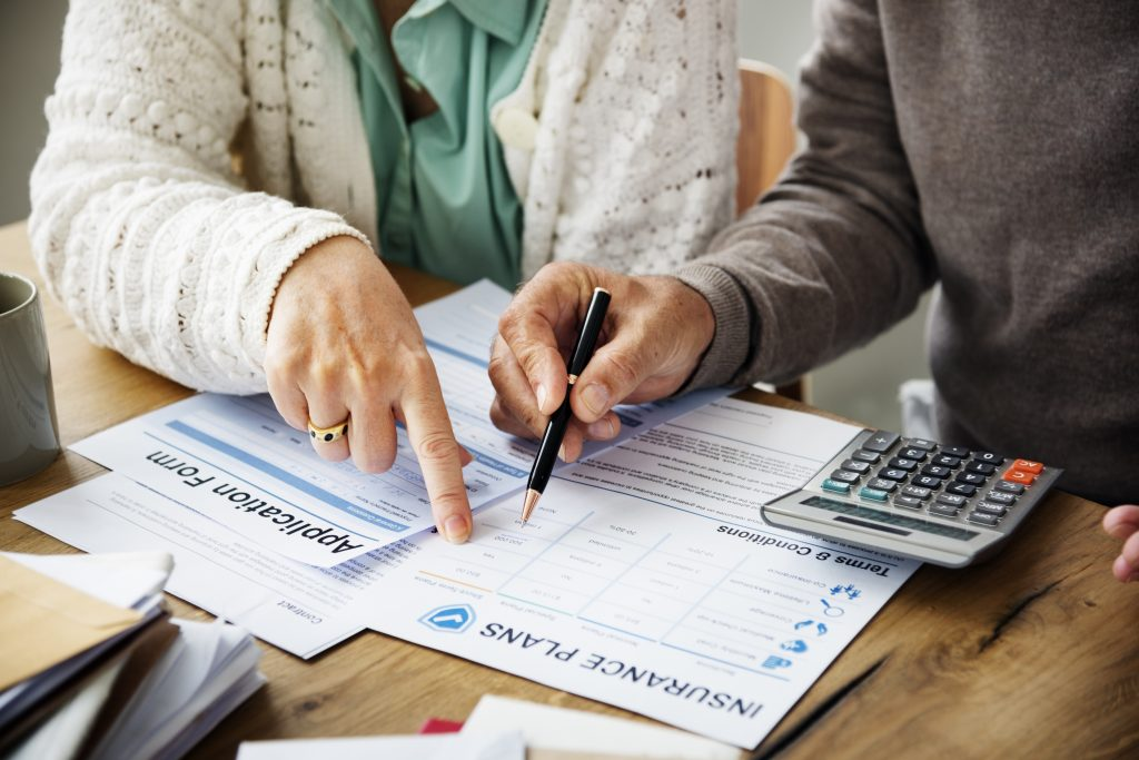 Two people filling out an application for insurance plans